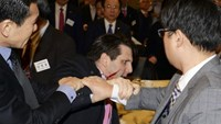 U.S. Ambassador to South Korea Mark Lippert leaves after he was slashed in the face by Kim Ki-jong, a member of a pro-Korean unification group, at a public forum in central Seoul in this handout picture provided by Munhwa Ilbo on March 5, 2015.