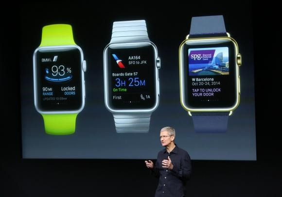 Apple CEO Tim Cook stands in front of a screen displaying apps available for the Apple Watch at a presentation at Apple headquarters in Cupertino, California October 16, 2014.