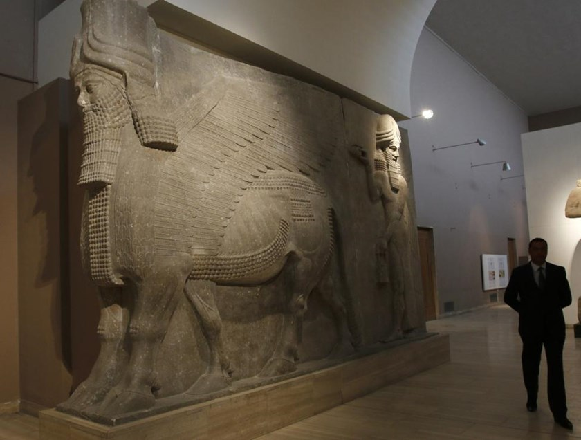 A man walks past human-headed winged bull statues from Khorsabad, at the Iraqi National Museum in Baghdad March 8, 2015.