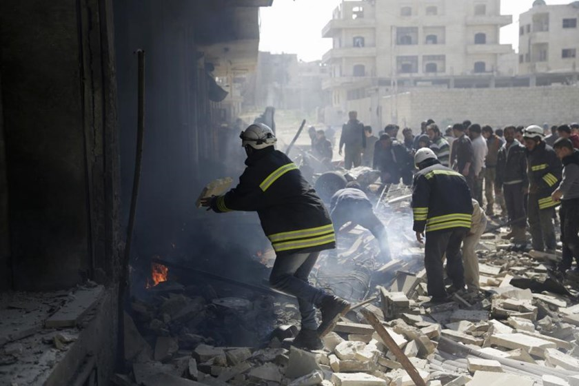 Civil defence personnel remove debris at a site damaged by what activists said was a car explosion near a Free Syrian Army headquarter in Maarat Al-Nouman, south of Idlib March 14, 2015.