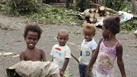 Children stand in front of debris on a street near their homes after Cyclone Pam hit Port Vila, the capital city of the Pacific island nation of Vanuatu March 15, 2015.