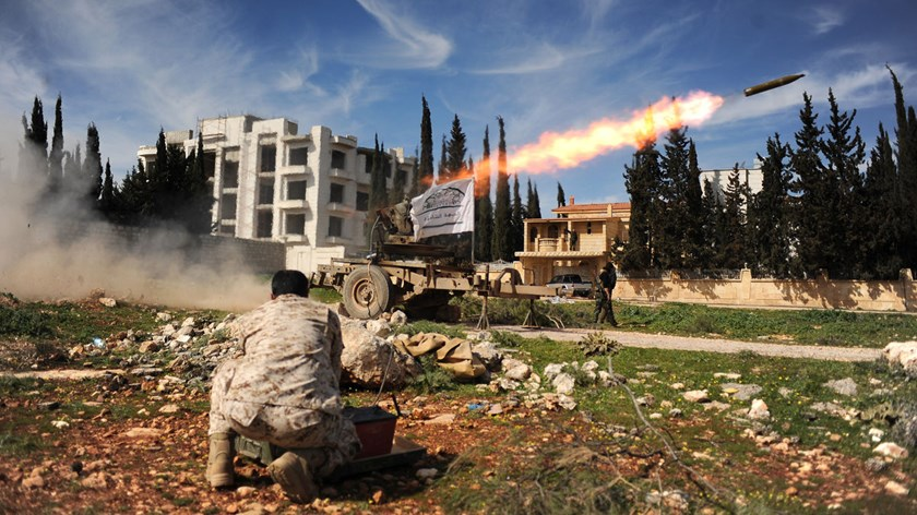 Members of a Syrian opposition group linked to the Damascus Front launch a rocket towards forces loyal to Syrian President Bashar al-Assad's regime during clashes in Aleppo, on March 7, 2015.