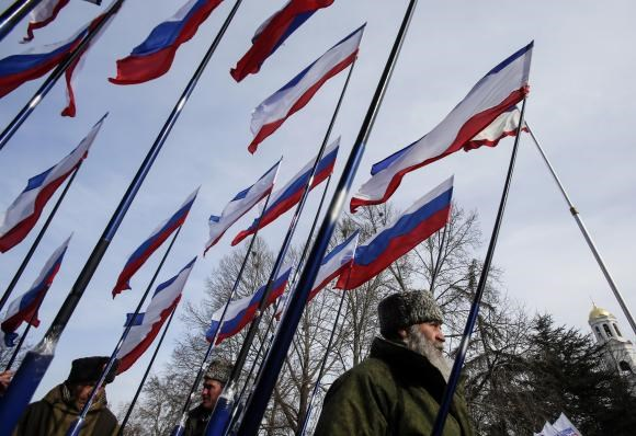 Members of self-defence units hold Russian and Crimean flags during a meeting to celebrate the first anniversary of Russia's annexation of Ukraine's Black Sea peninsula of Crimea, in central Simferopol March 16, 2015.