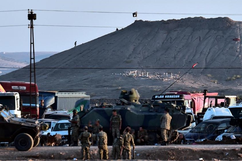 Islamic State militants (Rear) stand next to an IS flag atop a hill in the Syrian town of Ain al-Arab, known as Kobane by the Kurds, as seen from the Turkish-Syrian border in the southeastern town of Suruc, Sanliurfa province, on October 6, 2014