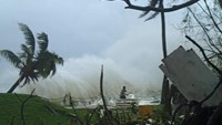Handout photo taken on March 14, 2015, by CARE Australia shows a man running away from high waves caused by Cyclone Pam crashing along the coast in the Vanuatu capital of Port Vila