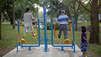 A young girl, right, watches an elderly man, center, exercise at Lumphini Park in Bangkok, on March 15, 2015. Almost a third of Thailand's population will be over 60 by 2050, compared with less than a sixth in the Philippines and a fifth in Malaysia, acco