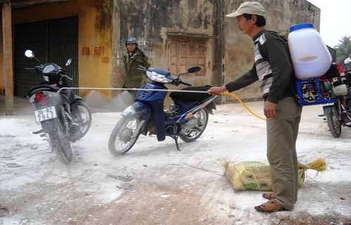A healthcare worker sprays disinfectant in the area they found birds infected with the pathogenic H5N6 bird flu virus in Thanh Hoa Province. Photo: Le Hoang
