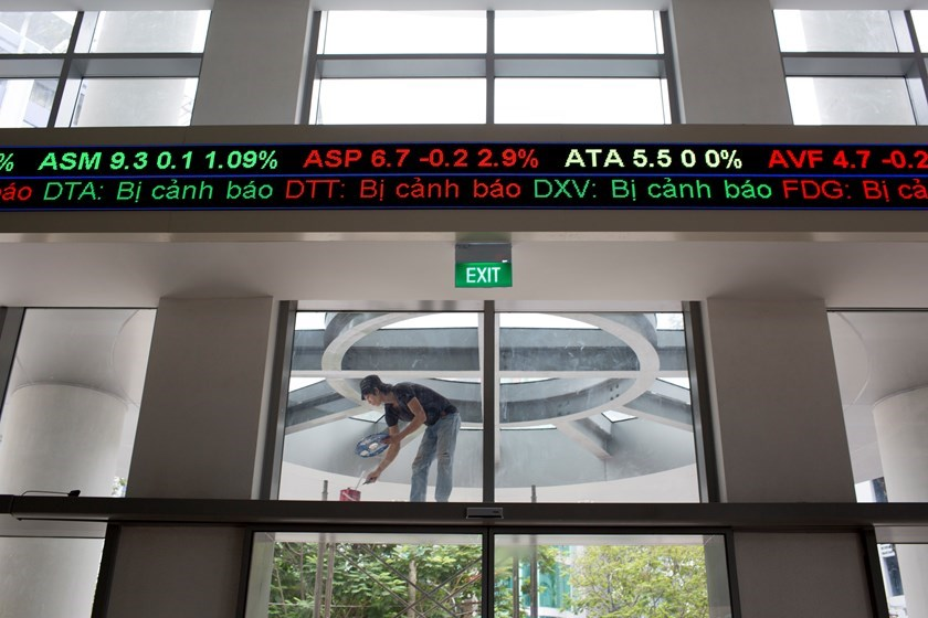 An electronic stock ticker displays share prices as a laborer paints outside the new Ho Chi Minh Stock Exchange (HOSE) in Ho Chi Minh City, Vietnam, on Monday, June 2, 2014. Photo: Bloomberg