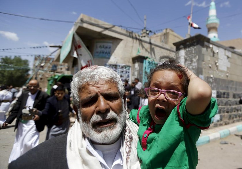An injured girl reacts as she is carried by a man out of a mosque which was attacked by a suicide bomber in Sanaa March 20, 2015.