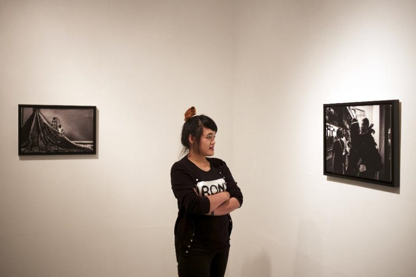 Filipino photographer Xyza Cruz Bacani poses with her work in Macau on March 21, 2015