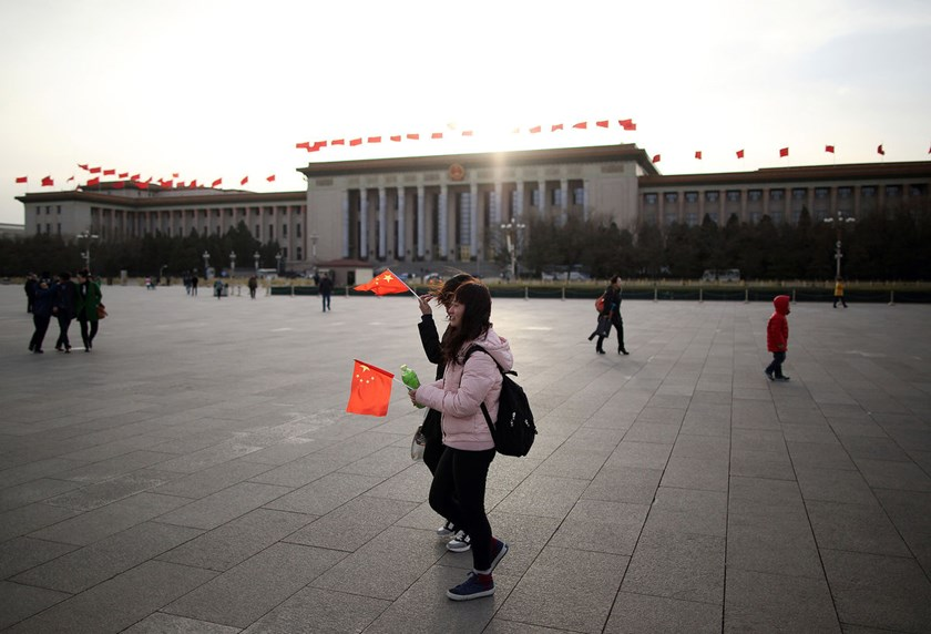 Pedestrians holding Chinese national flags walk past the Great Hall of the People in Beijing. China's clout has been expanding for decades.
