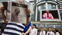 A monitor shows coverage of the death of Singapore's first elected Prime Minister Lee Kuan Yew as a man reads a special edition of a Today newspaper, produced by MediaCorp Press Ltd., at Raffles Place in Singapore.