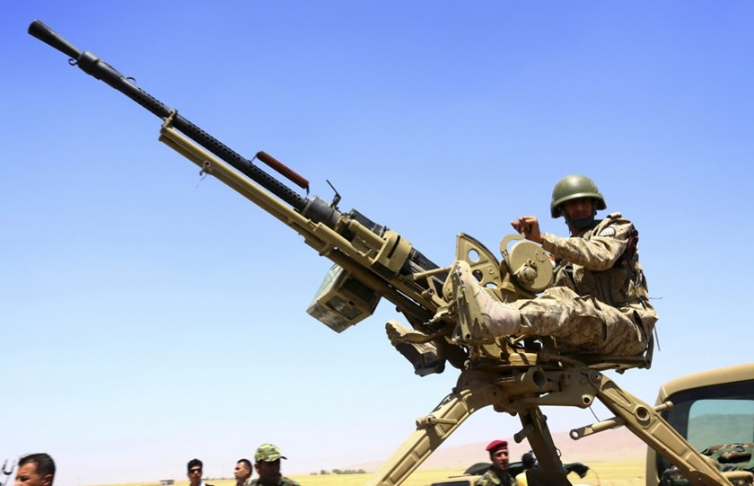 A member of the Kurdish peshmerga forces sit with a weapon during an intensive security deployment against Islamic State militants in Makhmur, on the outskirts of the province of Nineveh August 7, 2014.