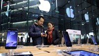 A couple look at an Apple Inc. iPhone 6 at an Apple store in the China Central Mall in Beijings.