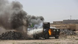 A military vehicle, belonging to Shi'ite fighters known as Hashid Shaabi, burns after being hit by Islamic State militants, during clashes in northern Tikrit, March 11, 2015.