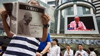 A monitor shows coverage of the death of Singapore's first elected Prime Minister Lee Kuan Yew as a man reads a special edition of a newspaper, at Raffles Place in Singapore, on March 23, 2015.