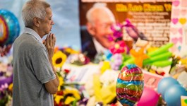 A mourner prays next to a floral tribute to Singapore's first elected Prime Minister Lee Kuan Yew following the announcement of his death, at Singapore General Hospital in Singapore, on March 23, 2015.