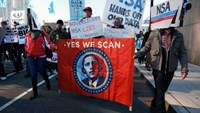 "Demonstrators wearing cardboard surveillance camera hats carry a sign depicting U.S. President Barack Obama at the ""Stop Watching Us: A Rally Against Mass Surveillance"" march in Washington, October 26, 2013"