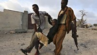 Residents evacuate an injured boy after Islamist group al Shabaab attacked Maka Al-Mukarama hotel in Mogadishu, March 27, 2015.