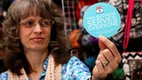 Elizabeth Ladd, owner of River Knits Fine Yarns, poses while holding up a 'This businesses serves everyone' sticker she plans to place outside her business in downtown Lafayette, Indiana March 31, 2015.