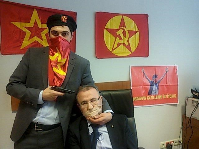 A gunman poses with Prosecutor Mehmet Selim Kiraz with a gun on his head after being taken hostage in his office in a court house in Istanbul March 31, 2015.