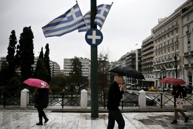 People holding umbrellas make their way next to fluttering Greek national flags on the main Constitution (Syntagma) square during heavy rainfall in Athens March 13, 2015.