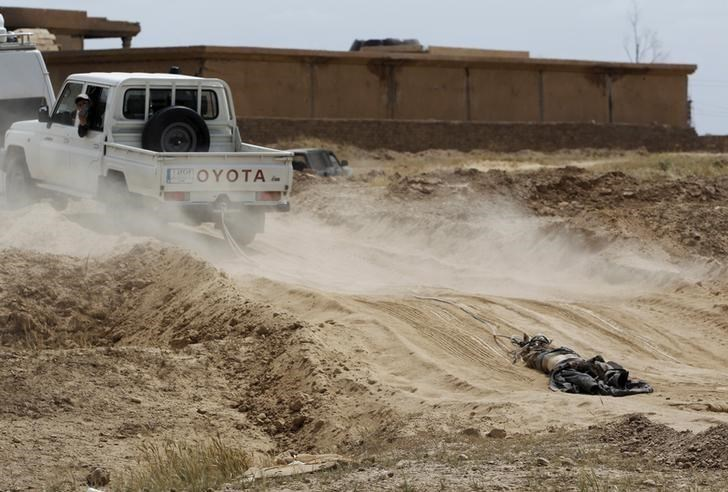 A vehicle belonging to Shi'ite militia fighters pulls the body of an Islamic State fighter, who was killed during clashes with Iraqi forces, in Tikrit April 1, 2015.