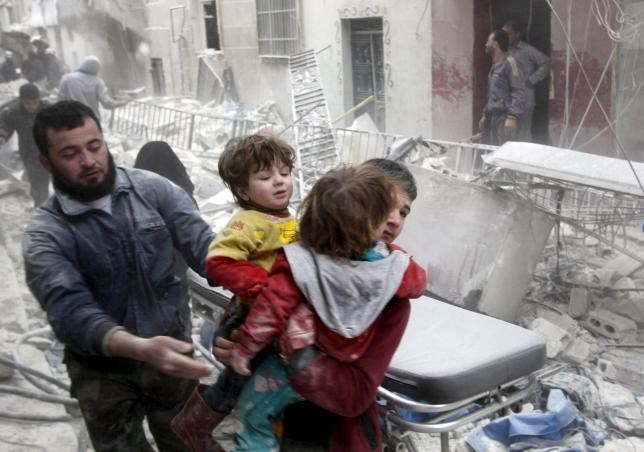 A boy carries two children as he evacuates them from a site hit by what activists said was a barrel bomb dropped by forces loyal to Syria's President Bashar al-Assad in Aleppo's al-Fardous district April 2, 2015.