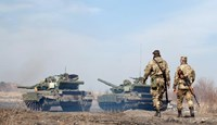 Ukrainian servicemen walk behind tanks as they take part in exercises near the eastern Ukrainian city of Lysychansk in the Lugansk region on March 27, 2015