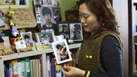 Jang Sun Bok holds a photo of her son, Jun Woo, who died on the Sewol ferry last year for a photograph at her home in Ansan, South Korea, on Friday, March 6, 2015.