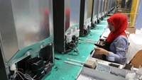 An employee installs components onto refrigerators on the production line at the Sharp Corp. factory in Karawang, Indonesia.