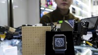 A salesman looks on as an Apple Watch look-alike device, made by a Chinese manufacturer, is displayed at a mall selling electronic products in China's southern city of Shenzhen, April 8, 2015.