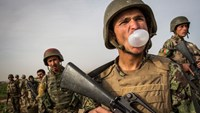 A soldier with the Afghan National Civil Order Police blows a bubble with his gum during a two-day, joint mission with the United States Army near Command Outpost Siah Choy in Kandahar Province, Afghanistan, on March 26, 2013.