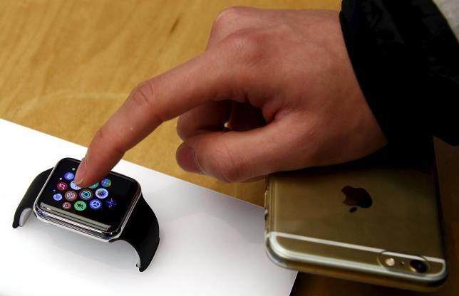 A customer holding his iPhone touches an Apple Watch after it went on display at the Sydney Apple store April 10, 2015.
