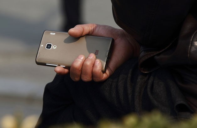 A man holds a Xiaomi Corp. branded smartphone in Beijing. Five years since its founding in 2010, Xiaomi has grown into China's top smartphone vendor and -- at $45 billion -- the world's most valuable startup.