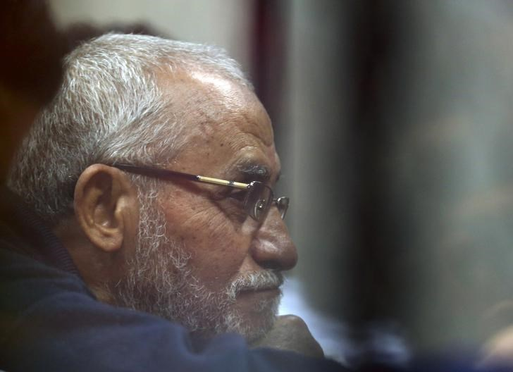 Muslim Brotherhood's Supreme Guide Mohamed Badie listens to lawyers as he sits behind bars during his trial with ousted Egyptian President Mohamed Mursi and other leaders of the brotherhood at a court in the police academy on the outskirts of Cairo Decemb