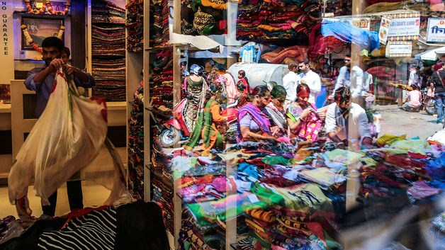 Customers browsing at a fabric stall are reflected in a store window at Mangaldas Market in Mumbai, India, on Feb. 26, 2015.