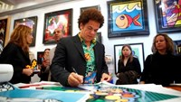 Artist Romero Britto signs posters at a gallery in New York April 2, 2009.