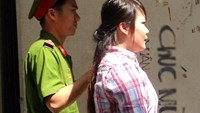 Nguyen Thi Kim Loan is escorted by a police officer to the HCMC People's Court on Wednesday