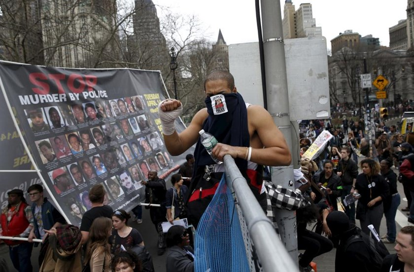 Demonstrators climb over a fence during a protest against police brutality against minorities in New York, April 14, 2015.