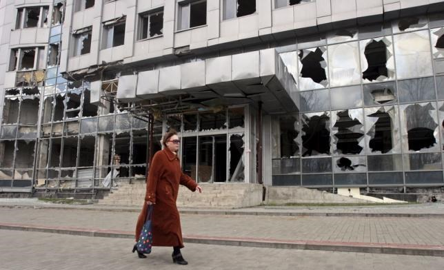 A woman walks past a building damaged by fighting in Donetsk, April 15, 2015.