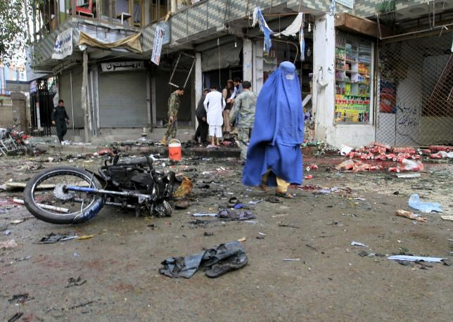An Afghan woman walks at the site of a suicide attack in Jalalabad April 18, 2015.