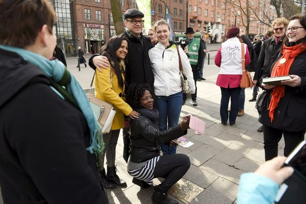 Juha Sipila, leader of the opposition Center Party, center, poses for a photo with passersby during an election campaign in Helsinki on April 14.