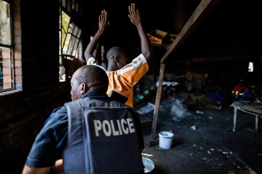 A resident raises his hands as a South African anti-riot police officer raids a hostel in Benoni on April 16, 2015