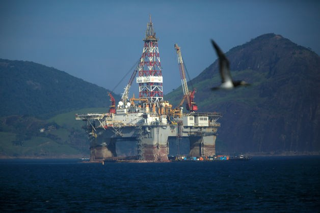 A bird flies past an oil drilling platform in Guanabara Bay near Niteroi, Brazil, on Monday, April 20, 2015.