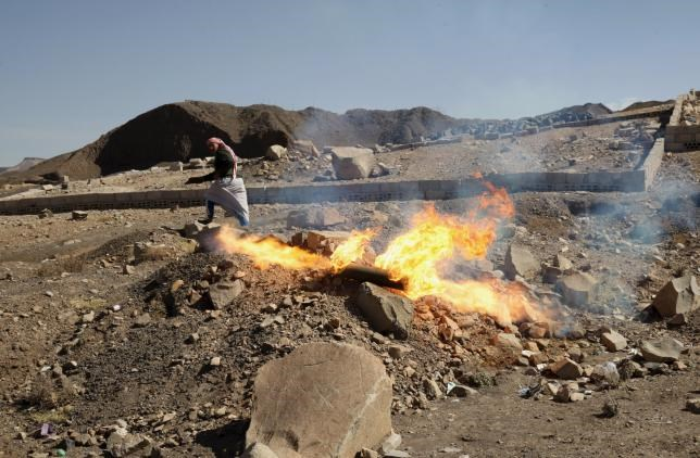 A man flees after igniting an unexploded shell which landed from a nearby missile base after the base was struck by a Saudi-led coalition air strike, near Sanaa April 23, 2015.