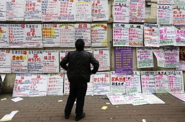 A man looks at job information at an employment fair beside a street in Zhengzhou, Henan province, February 19, 2014.