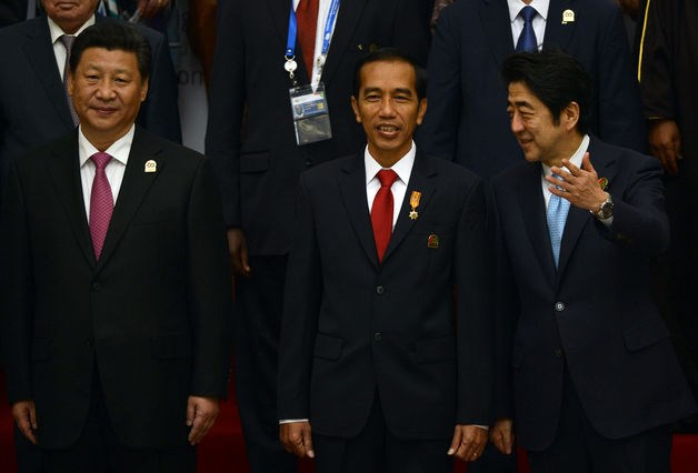 China's President Xi Jinping, left, Indonesia's President Joko Widodo, center, and Japanese Prime Minister Shinzo Abe, pose for photographs during the opening of Asian African Conference in Jakarta on April 22, 2015.