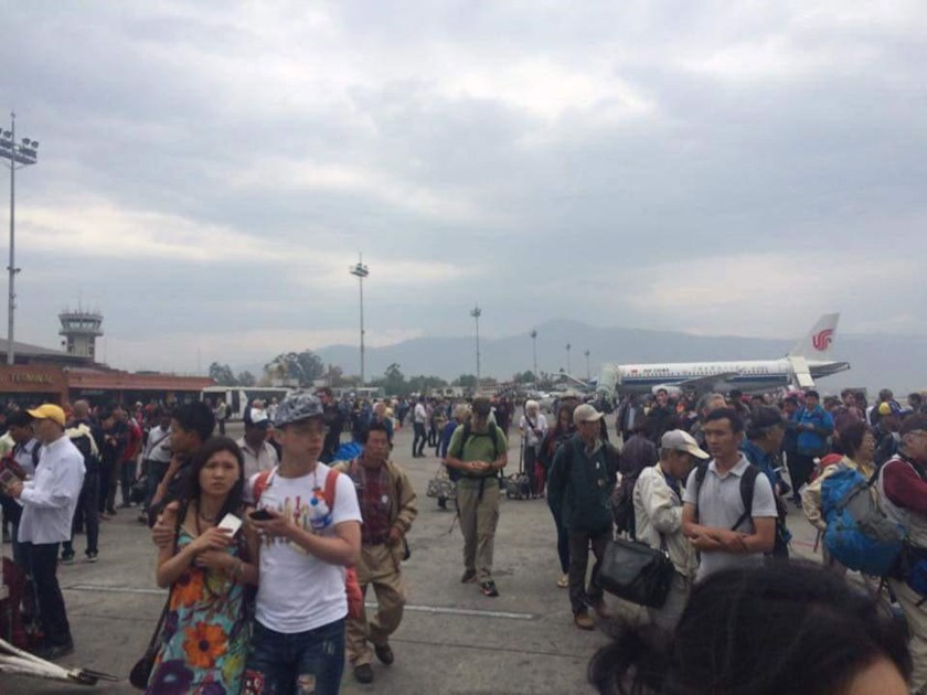 People stand on the runway outside the International Terminal after a earthquake hit, at Tribhuvan International Airport, Kathmandu, Nepal, April 25, 2015, in this handout courtesy of Dhany Osman.