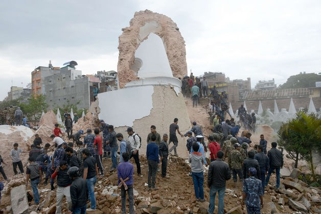 Nepalese rescue workers and onlookers gather at the collapsed Darahara Tower in Kathmandu on April 25.